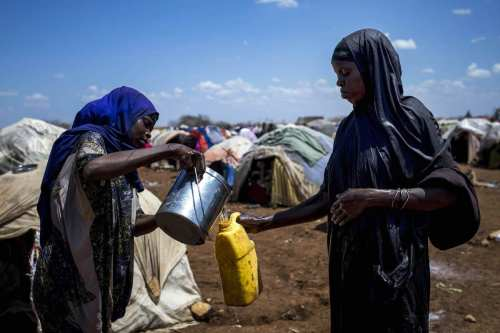 A Somalian woman fills her plastic bottles with water at Dakamur camp in Somalia's Bay state on March 27, 2017 [Arif Hüdaverdi Yaman/Anadolu Agency]