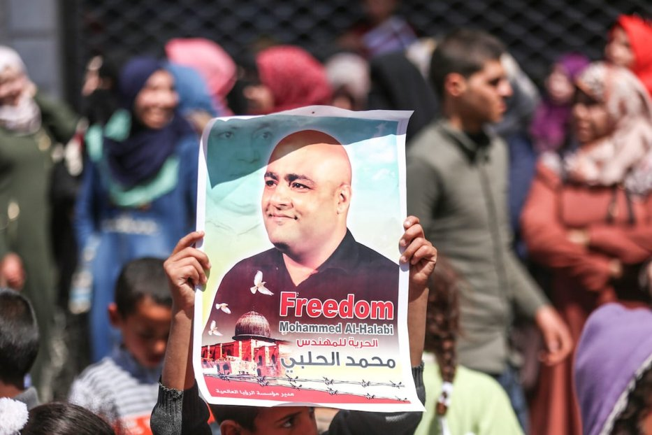 Palestinian protesters hold posters of Mohammad El Halabi, World Vision International's manager of operations in Gaza who was arrested by Israeli forces in Gaza City, Gaza on March 28, 2017 [Mustafa Hassona/Anadolu Agency]