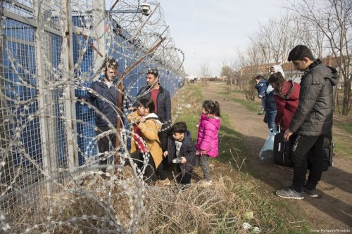 Syrian refugees wait next to the border gate between Hungary and Serbia on 23 March 2017 [Omar Marques/Anadolu Agency]