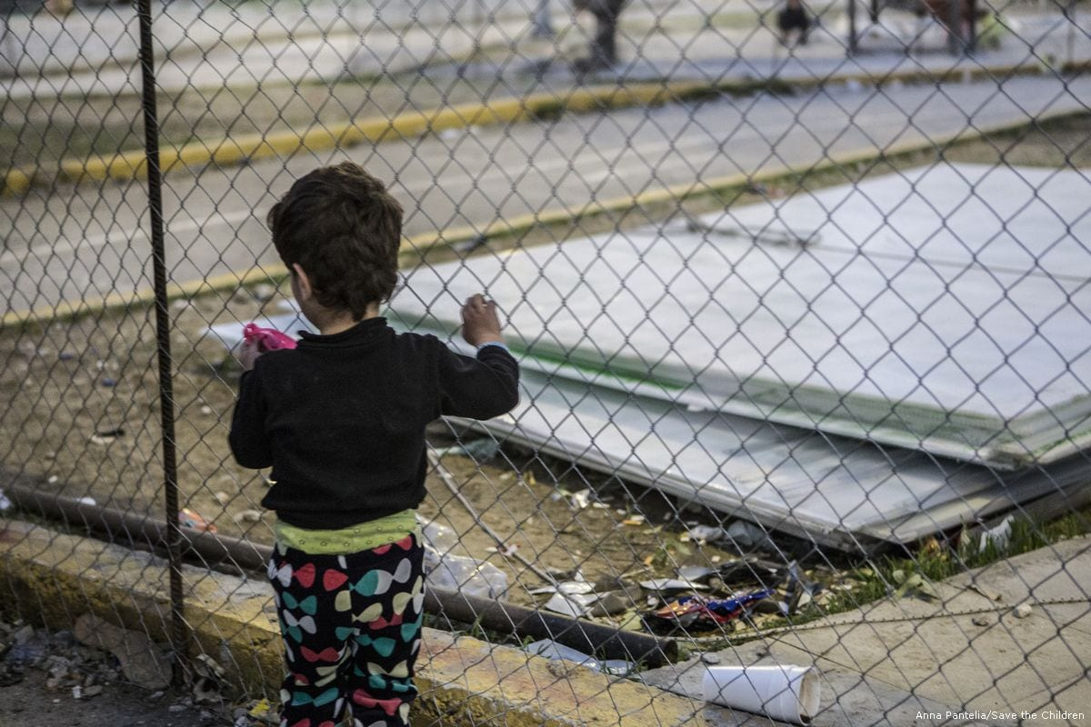 A young girl holds the fence in kara Tepe camp in Lesvos, Greece [Anna Pantelia/Save the Children]