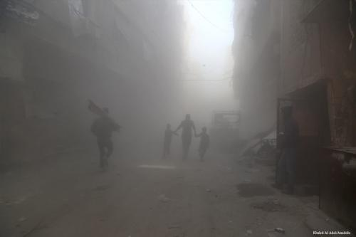 Syrians run through thick smoke due to the airstrikes carried out by the Assad Regime in Damascus, Syria on 29 March 2017 [Khaled Al Adel/Anadolu]