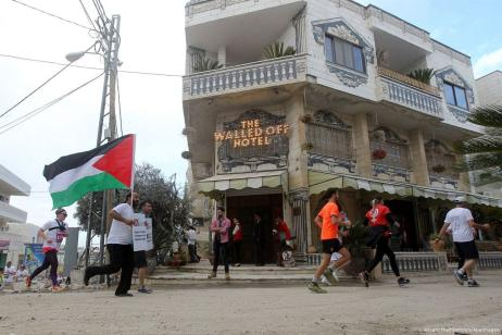 Participants run past the the Walled-Off Hotel, Banksy's newly opened hotel in Bethlehem, West Bank on March 31, 2017. [Wisam Hashlamoun/Apaimages]