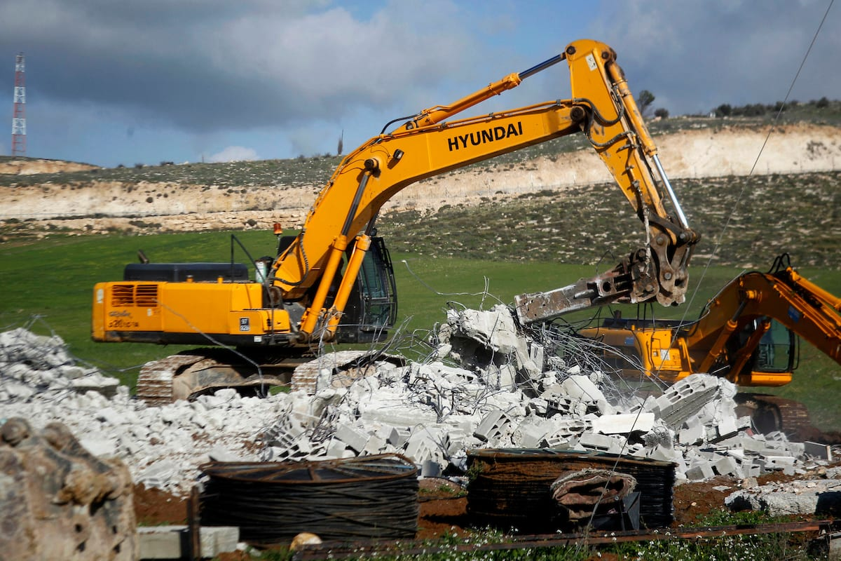 An Israeli bulldozer demolishes a Palestinian house [Wisam Hashlamoun/Apa Images]
