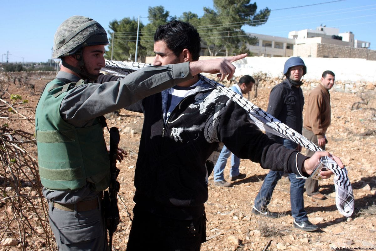 An Isreali soldier scuffles with Palestinian youth during a protest on 17 December 2010. [Najeh Hashlamoun/Apaimages]