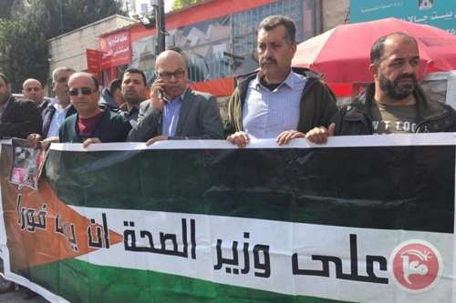 Palestinian protestors hold up signs during the protest in Beit Jala hospital against alleged medical negligence, corruption