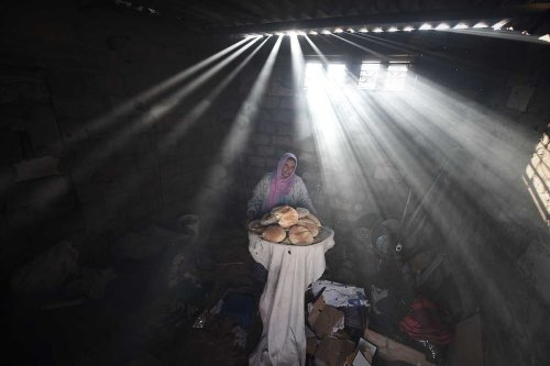 A Palestinian woman bakes bread despite the power cut and lack of gas in Khan Yunis, Gaza on April 19, 2017 [Abed Zagout/Anadolu Agency]