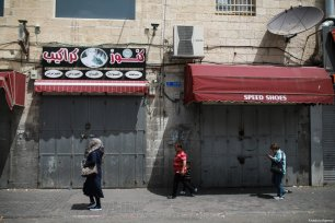 An old woman passes by a closed shop in Jerusalem on April 27, 2017 [Mostafa Alkharouf/Anadolu Agency]