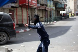 A Palestinian man throws stones at Israeli Security Forces during a demonstration in support of Palestinian prisoners in Israeli jails, in Hebron, West Bank on April 27, 2017. ( Mamoun Wazwaz - Anadolu Agency )