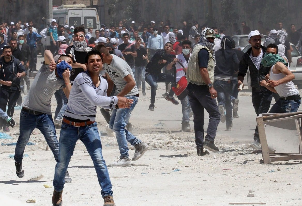 Palestinian protesters throw stones as Israeli Army violently disperses the crowd using plastic bullets and tear gas during a protest against building of Jewish settlements and separation wall at Kafr Qaddum village of Nablus, West Bank on April 28, 2017. [Nedal Eshtayah/Anadolu Agency]