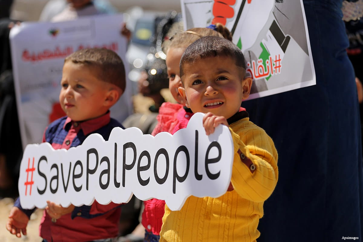 "Palestinian activists take part in a rally titled ""Save Pal People"" against the Israeli occupation and Gaza blockade in front of a tower which was destroyed during the 50-day war between Israel and Hamas in the summer of 2014"