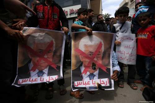 Hamas supporters carry posters depicting Palestinian President Mahmoud Abbas with a red cross during a protest in Khan Younis, Gaza Strip on 14 April 2017 [Ashraf Amra/Apaimages]