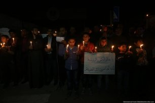 Childrens are seen holding candles in order provide light as Gaza's Energy authority goes on strike due to salary cuts by the PA on 14 April 2017. [Images by Mohammad Asad / Middle East Monitor]