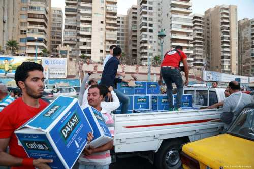 Egyptians carry boxes of bottled water on 26 June 2015 [Amr Sayed/Apaimages]