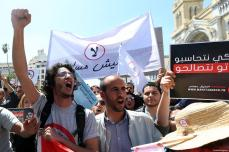 People hold banners during a protest against government's bill on Economic and Financial Reconciliation in Tunis, Tunisa on April 29, 2017 [ Yassine Gaidi / Anadolu Agency]