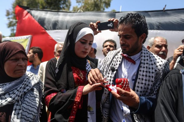 Gazaian Said Lulu (2nd R) and Halud Dervis (R) are seen during their wedding ceremony in Gaza on May 8, 2017 [Ali Jadallah/Anadolu Agency]