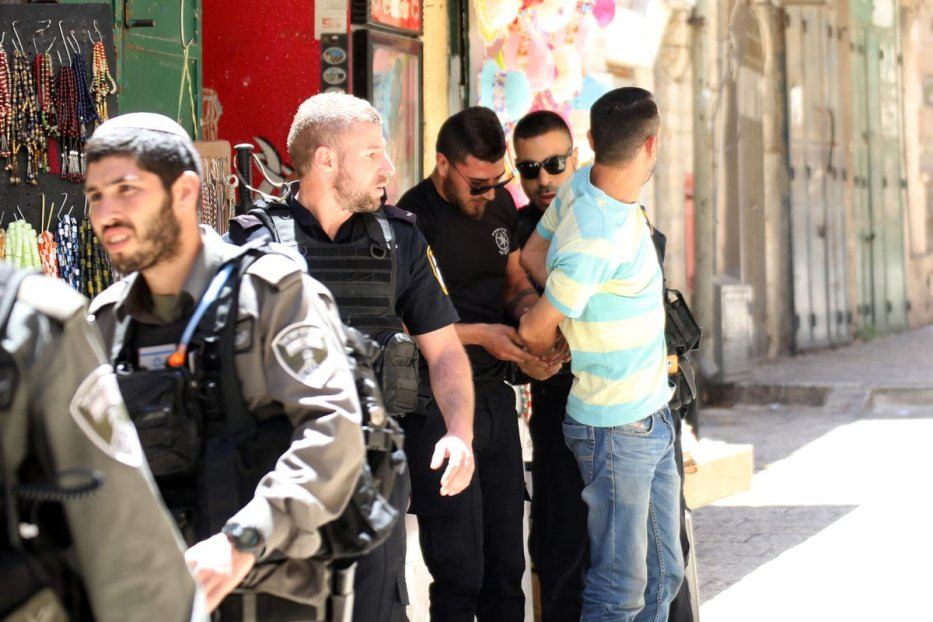 Israeli security forces take a Palestinian man into custody, who entered into the crime scene, as they inspect the crime scene after a Jordanian man was shot dead in an alleged stabbing attack in East Jerusalem, on 13 May, 2017 [Mostafa Alkharouf / Anadolu Agency]