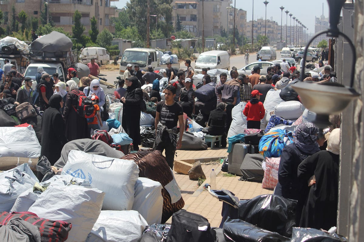 Syrian civilians and opposition forces wait to be evacuated from Al-Waer district of Homs, Syria on 15 May 2017 [Judy Arash/Anadolu Agency ]