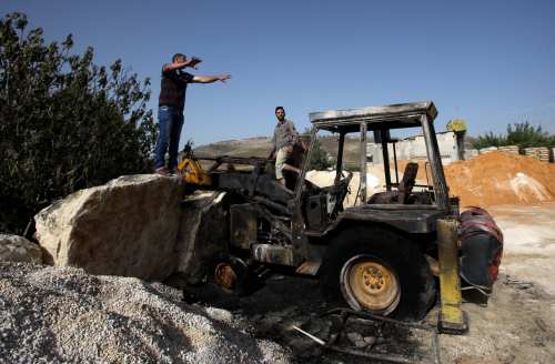 Palestinian men inspect the construction equipment which was set on fire by Jewish settlers, in Nablus, West Bank, on May 18, 2017 [Nedal Eshtayah/Anadolu Agency]