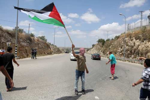 Palestinians blocking the road during a demonstration to show solidarity with hunger striker Palestinian prisoners in Israeli jails at the Ni'lin village in Ramallah, West Bank on 19 May, 2017 [Issam Rimawi/Anadolu Agency]