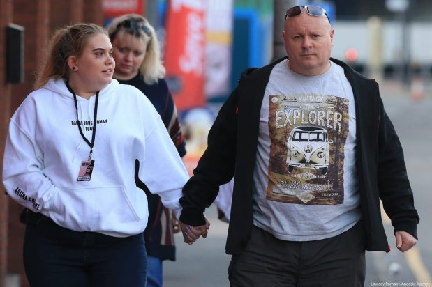 A young victim, still wearing her concert sweater and concert badge, hold her father's hand as she leaves the Park Inn hotel that took-in victims from the Manchester Arena stadium in Manchester, United Kingdom on 23 May 2017. A large explosion was reported at the end of a concert by American singer Ariana Grande. [Lindsey Parnaby/Anadolu Agency]