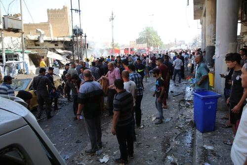 People gather around the incident site as security forces cordon the area after a road-side parked car-bomb attack in Baghdad, Iraq on 30 May, 2017 [Visam Ziyad Muhammed/Anadolu Agency]