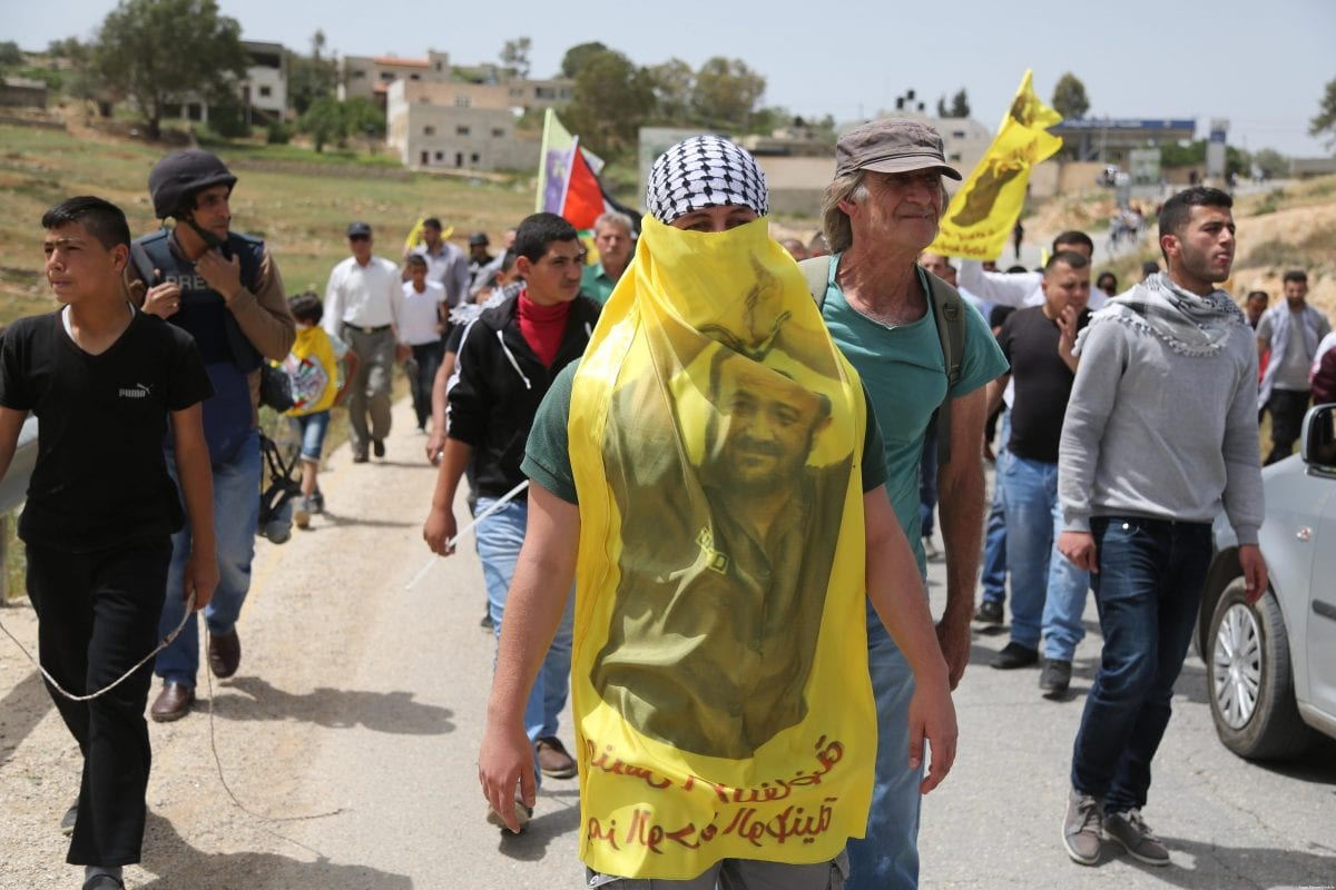 A Palestinian protester seen with a banner of Marwan Barghouti, during a demonstration organised to show solidarity with hunger-striker prisoners in Ramallah, West Bank on April 21, 2017 [Issam Rimawi/Anadolu Agency]