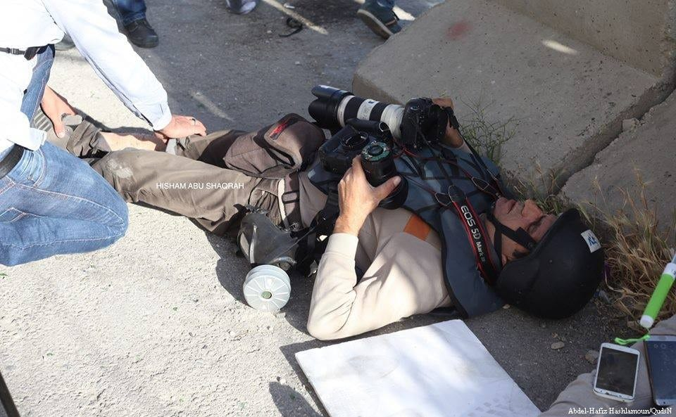 Palestinian journalists injured by stun grenades used by the occupation forces covering protests in support of prisoners in the occupied West Bank city of Bethlehem on 4 May 2017 [Abdel-Hafiz Hashlamoun/Safia Omar]