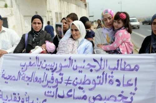 Syrian refugees in Morocco hold up a banner asking for basic rights including access to medical care and aid on 12 May, 2017 [Masr Al-Arabiya]