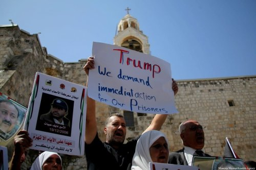 Palestinian demonstrators hold banners and posters during a demonstration in support of the Palestinian prisoners held in Israeli jails, outside the Mahd Church as U.S. President Donald Trump meets Palestinian President Mahmoud Abbas in Bethlehem, West Bank on May 22, 2017 [Mamoun Wazwaz/Anadolu Agency]