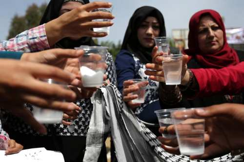 Palestinians drink water and salt during a protest in solidarity with Palestinian prisoners on hunger strike in Israeli jails in Gaza on 30 April 2017 [Ashraf Amra/Apaimages]