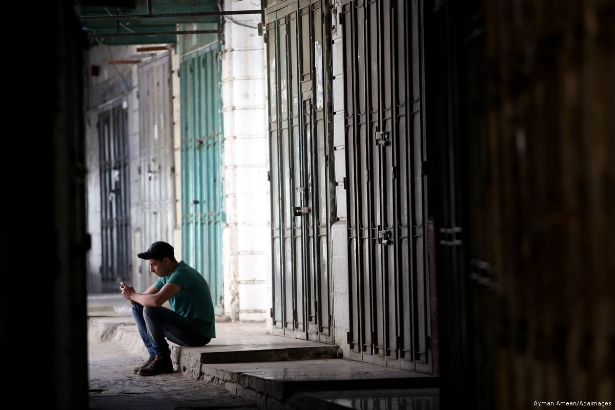 A Palestinian boy sits in front of closed shops during a general strike in support of Palestinian prisoners on hunger strike in Israeli jails on May 22, 2017 [Ayman Ameen/Apaimages]