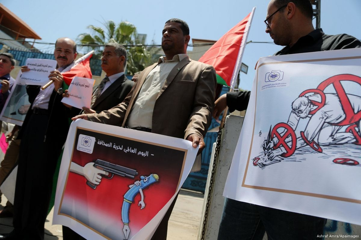 Palestinian journalists hold banners during a protest against Israeli violence towards journalists on World Press Freedom day in Gaza on 3 May 2017 [Ashraf Amra/Apaimages]