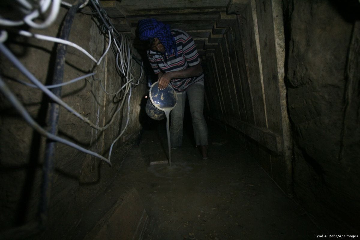 A Palestinian tunnel worker uses a bucket to empty water from a smuggling tunnel dug beneath the Gaza-Egypt border on 10 September 2013 [Eyad Al Baba/Apaimages]