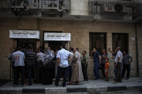 Public officials withdraw money after the Palestinian government applied a 30 per cent wage deduction from Public officials salaries in Gaza on June 1, 2017 [Ali Jadallah/Anadolu Agency]