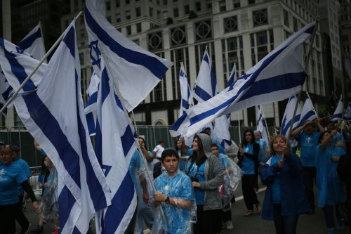 "Protester hold Israeli flags and signs during a ""Celebrate Israel"" parade in New York, US on June 4, 2017 [Mohammed Elshamy/Anadolu Agency]"