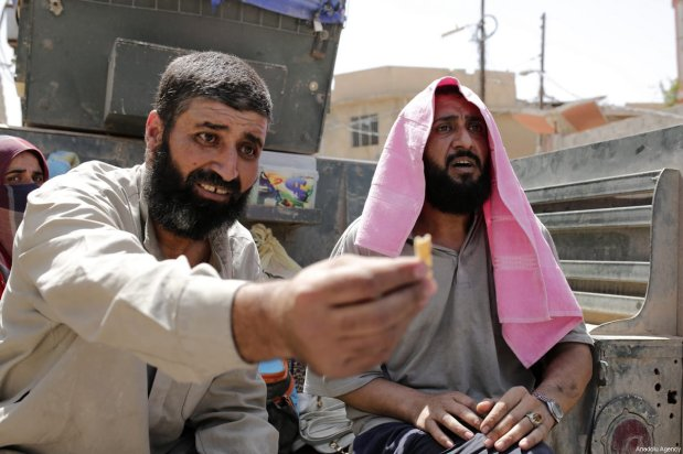Umid Ali Halef (L), a man who fled from the conflicts at al-Shifa neighbourhood in west, shows a piece of breadcrumb as he sits on back of an armored vehicle in Mosul, Iraq on June 12, 2017. Haled said: him and his family were stuck in their home due to a Daesh blockade and ate breadcrumbs to survive for 21 days. Civilians who fled the conflicted or Daesh blocked areas reached out to Iraqi army controlled Zencili neighborhood of Mosul and were transported from this area with armored vehicles as operation to liberate Iraq's Mosul from Daesh continues [Yunus Keleş / Anadolu Agency]