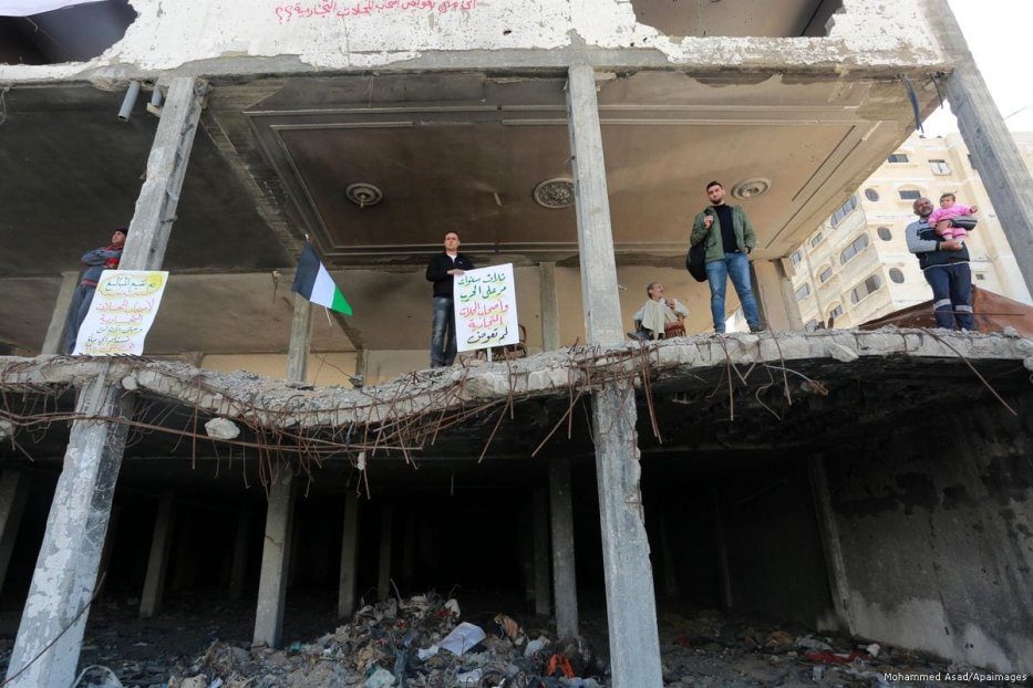 Palestinian activists demonstrate against the Israeli occupation and Gaza blockade in front of a tower which was destroyed during the 2014 war between Israel and Hamas in Gaza city on 1 April 2017 [Mohammed Asad/Apaimages]