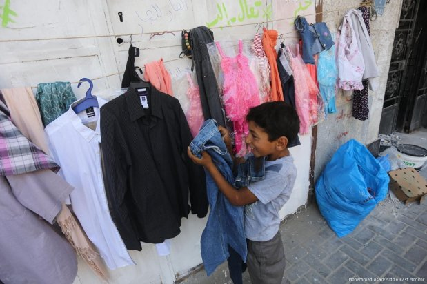 A pick me up. A child finds a pair of jeans amongst the items on offer at the 'Wall of Blessings' in the Gaza Strip on 23 June 2017 [Mohammed Asad/Middle East Monitor]