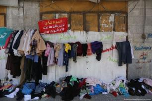 'A wall for all: Donate whatever you like and take whatever you like' is displayed at the 'Wall of Blessings' in the Gaza Strip on 23 June 2017 [Mohammed Asad/Middle East Monitor]