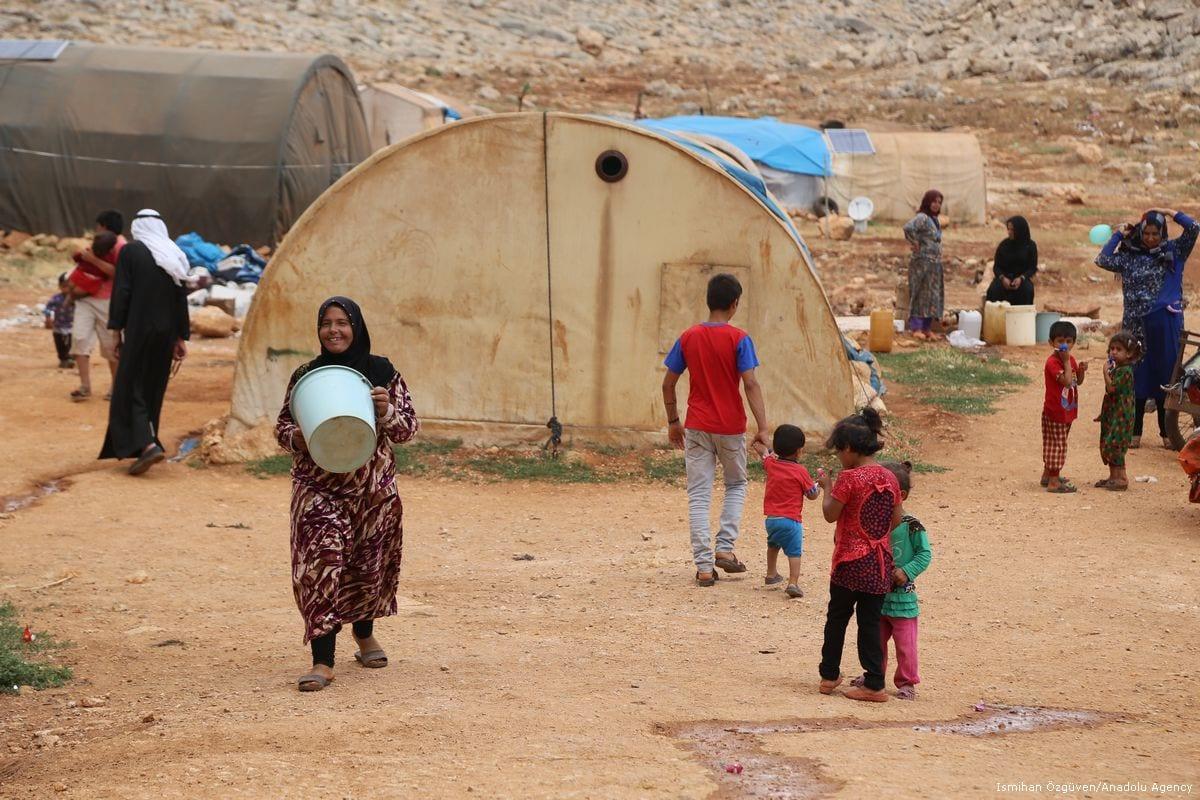 A Syrian woman carries a bucket fill with water in preparation of Eid in Idlib, Syria on 23 June 2017 [İsmihan Özgüven/Anadolu Agency]