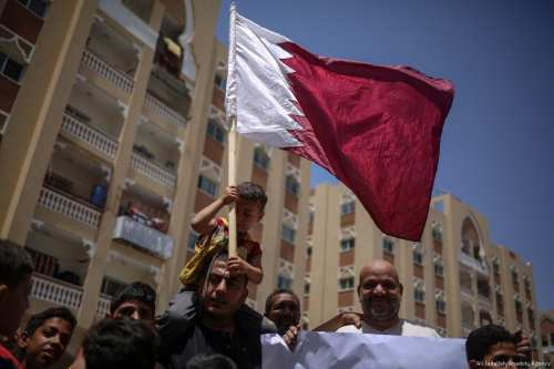Palestinian people hold flags and banners during a demonstration in support of Qatar, in Gaza on 9 June 2017 [Ali Jadallah/Anadolu Agency]