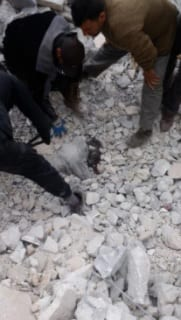 Rescuers recover the body of a child from the rubble of the mosque [Bilal Abdul Kareem]