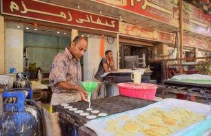 CAIRO, EGYPT- A street vendor prepares traditional sweets called Atayef