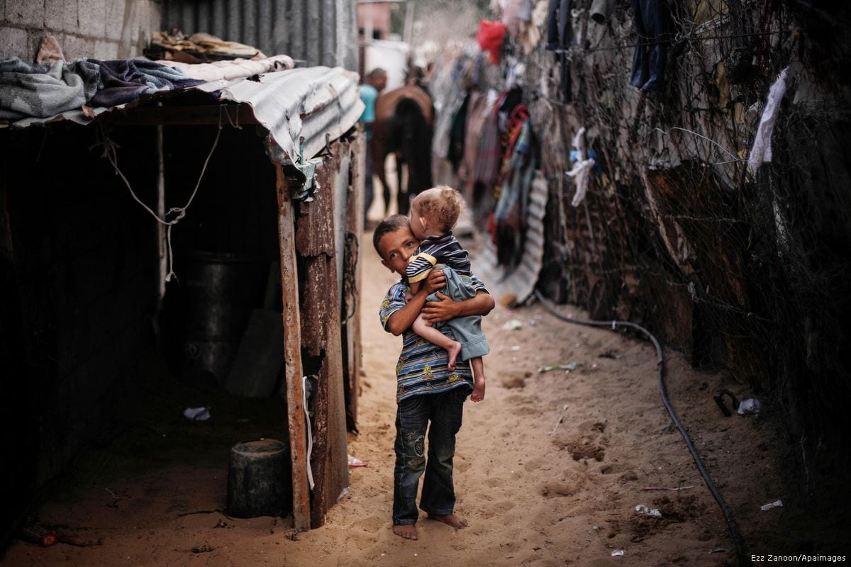 A Gazan boy walks with his younger sibling through their poverty stricken neighbourhood in Gaza on 4 September 2013 [Ezz Zanoon/Apaimages]