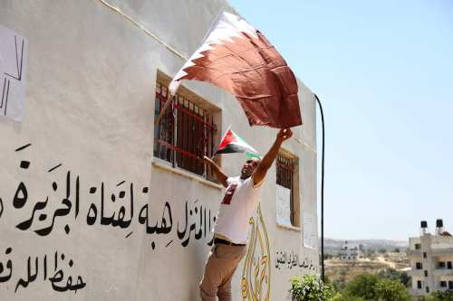 A Palestinian man hangs Qatari and Palestinian flags to the window of a house after the owner donated it to the Doha-based Al Jazeera channel to show solidarity with Qatar in Ramallah, West Bank on 2 July 2017 [Issam Rimawi/Anadolu Agency]