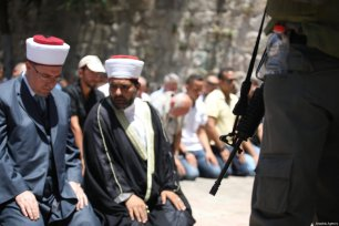 Sheikh Omar Qiswani, head of the Islamic Waqf (R) and worshippers perform prayers outside one of the main entrances to the Al-Aqsa mosque, refusing to enter because of new metal detectors installed at entrances as the holy site re-opened for the first time on Sunday since a two-day closure following a deadly shootout in Jerusalem on July 16, 2017 [Mostafa Alkharouf / Anadolu Agency]
