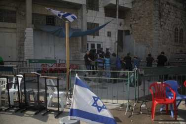 Israeli flags can be seen around a Palestinian house which was illegally occupied by settlers under the protection of occupation forces in the West bank city of Hebron on 26 July 2017. [Mamoun Wazwaz /Anadolu Agency]