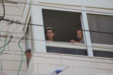 Settlers are seen looking out of the window of a Palestinian house one day after they took it over and evicted the Palestinian family which owns the property on 26 July 2017. [Mamoun Wazwaz /Anadolu Agency]