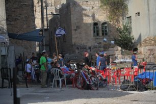 Settlers gather outside a Palestinian home after they evicted its legal owners and took it over in the occupied West Bank city of Hebron on 26 July 2017. [Mamoun Wazwaz /Anadolu Agency]