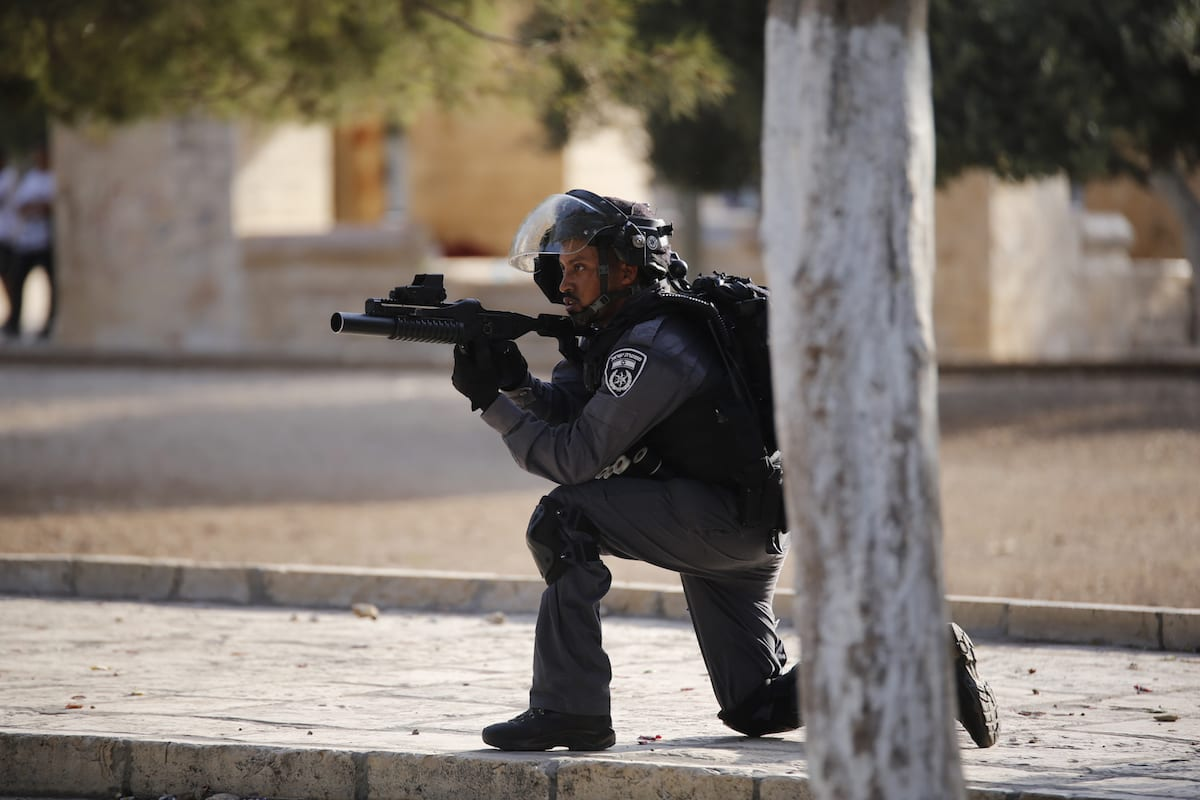 An Israeli solider aims his gun at Palestinians during a clash between Palestinians and Israeli forces [Mostafa Alkharouf/Anadolu Agency]
